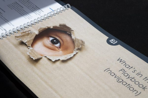 An eye close up peeks through a ripped hole in a cardboard box