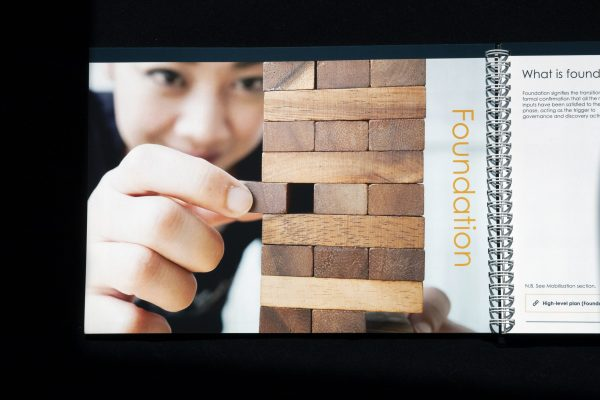 A boy delicately pulls out a wooden Jenga piece from a delicately balanced tower