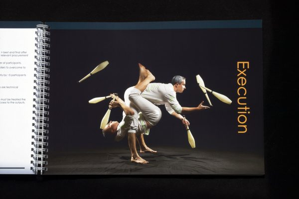 Two acrobats executing a complex juggling act with skittles